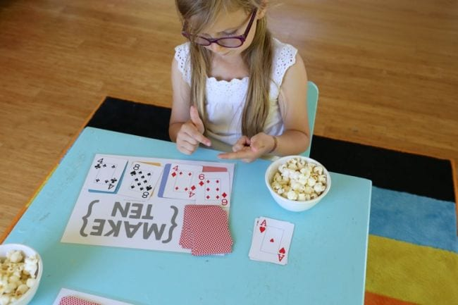 Student using playing cards and free printable worksheet to play Make Ten