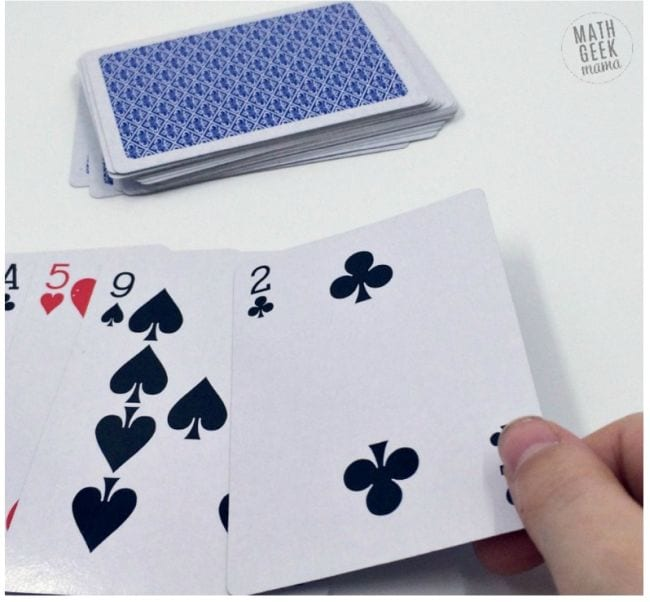 Student laying out playing cards to represent the digits of pi