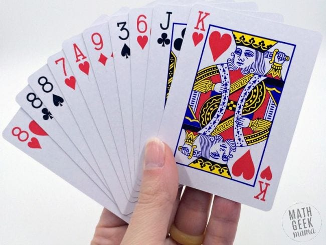 Student holding a selection of playing cards (Math Card Games)
