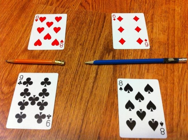 Two sets of playing cards laid out with pencils to create fractions