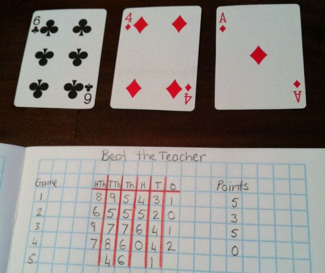 Four playing cards above a chart of place values