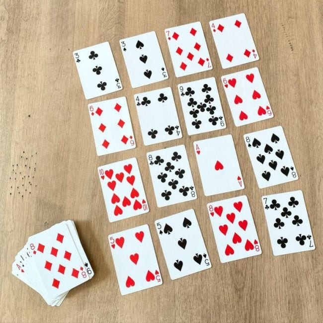 Playing cards laid out face up in four rows of four, with a deck next to it (Math Card Games)