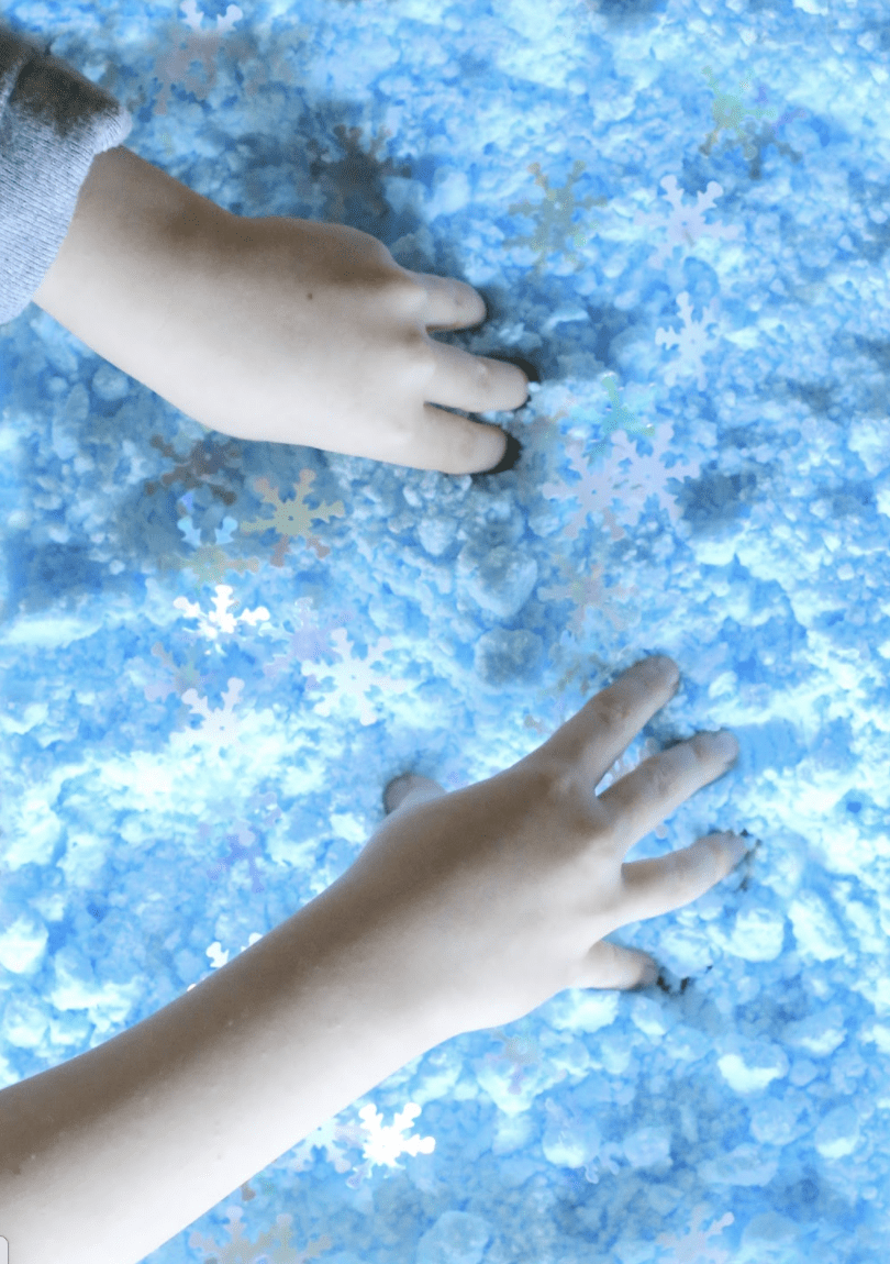 a student's hands playing in fake blue snow.