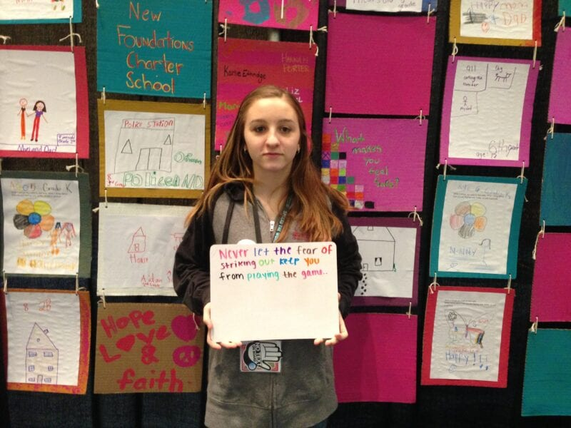 Student holds a card created for service-learning project with Judi's House.