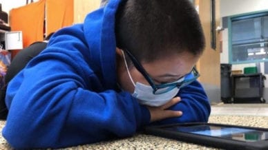 A student wearing a mask getting reading support from Bookshare.