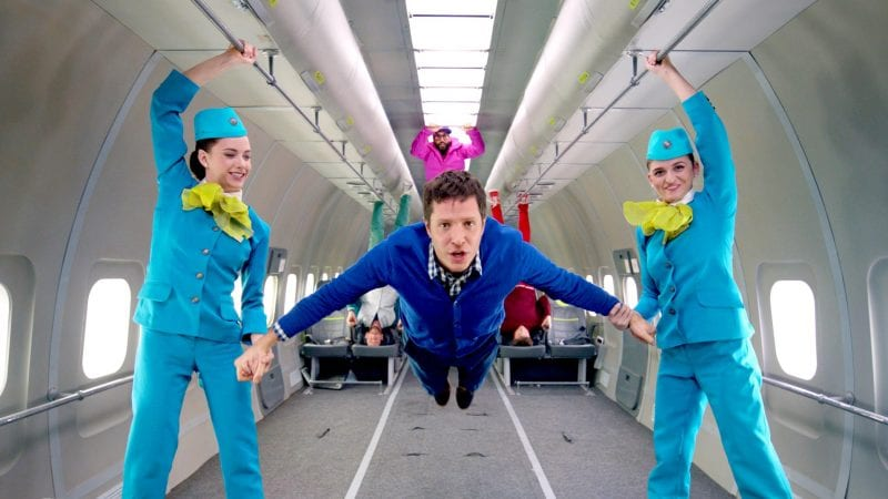 OK Go music video, a man floating with two women on either side of him.