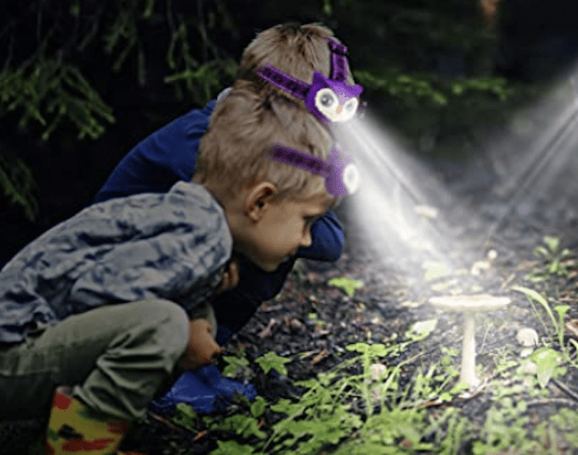 Two boys wearing headlamps and exploring outside at night, as an example of educational outdoor toys
