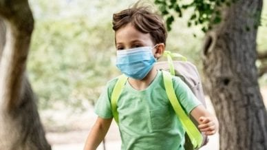 A young boy running with a mask on with a backpack on.