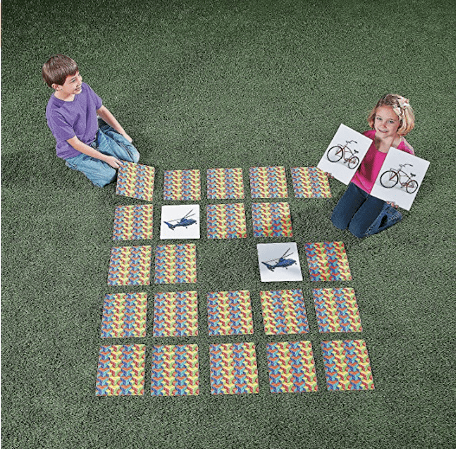 A boy and girl playing an outdoor memory game