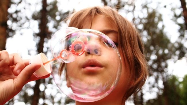 Student blowing a soap bubble through a bubble wand