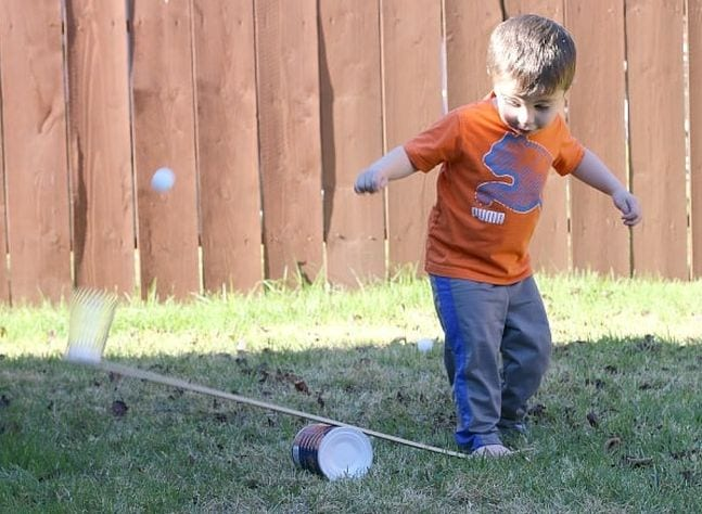 Child stomping on one side of a catapult made with a can and board, launching a ping pong ball into the air