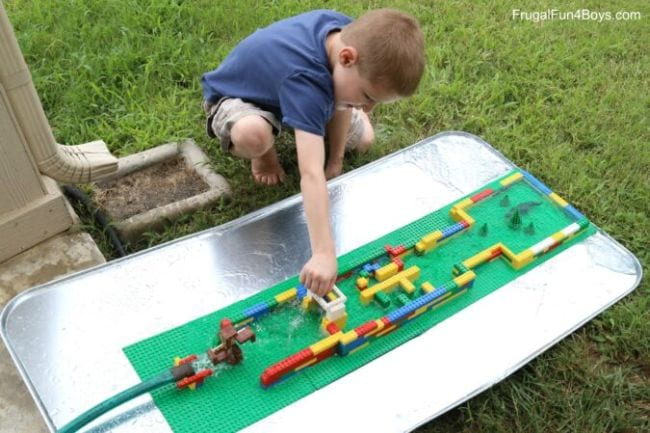 Child playing with a water course built from LEGO bricks (Outdoor Science)