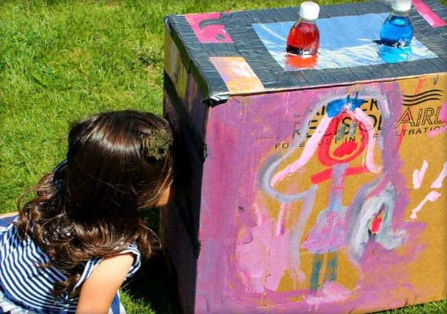 Student peering into a painted cardboard box with red and blue water bottles inserted into the top