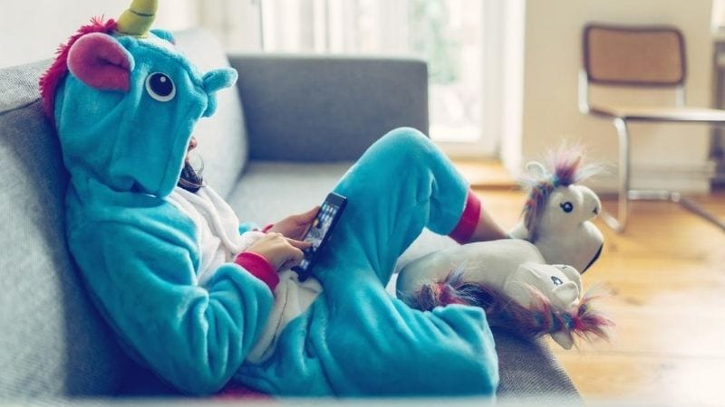 A young girl dressed up in a unicorn costume while playing on her phone.