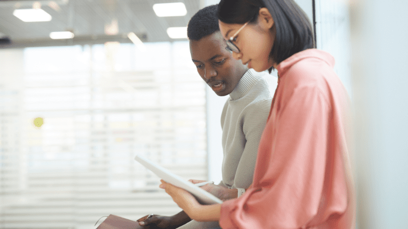 Young Black man and young Asian woman look over a paper together