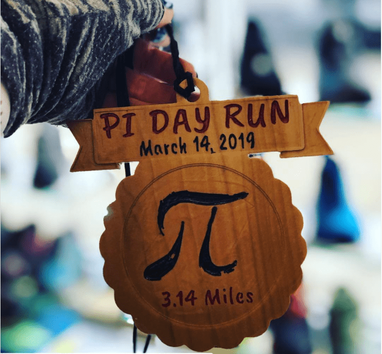 Wood plaque with the pi symbol, 3.14 miles and Pi Day Run title