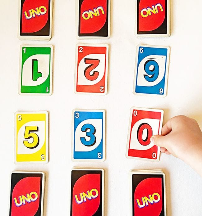 Student's hand laying out UNO cards in three rows