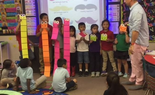 Kindergarten students holding large paper base ten blocks to represent the number 44 (Place Value Activities)