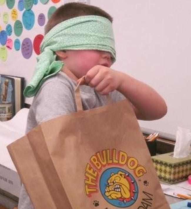 Student wearing a cloth blindfold and reaching into a paper bag