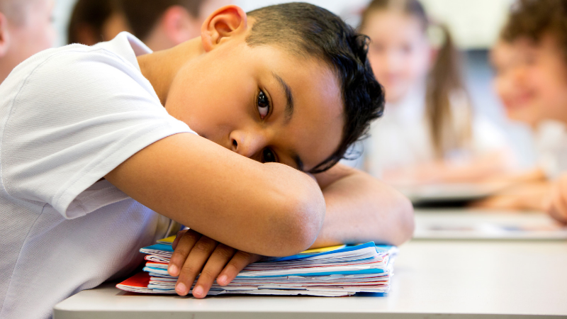 young hispanic boy with head down on his desk at school - Classroom Trauma Triggers