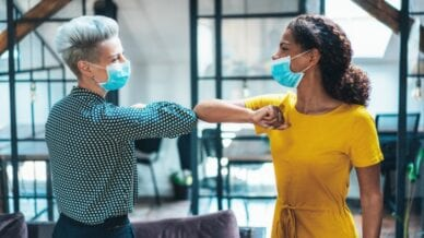 Two female colleagues at work with masks on giving each other an elbow bump