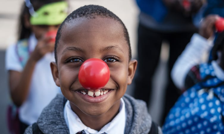 A young boy wearing a red nose on Red Nose Day.