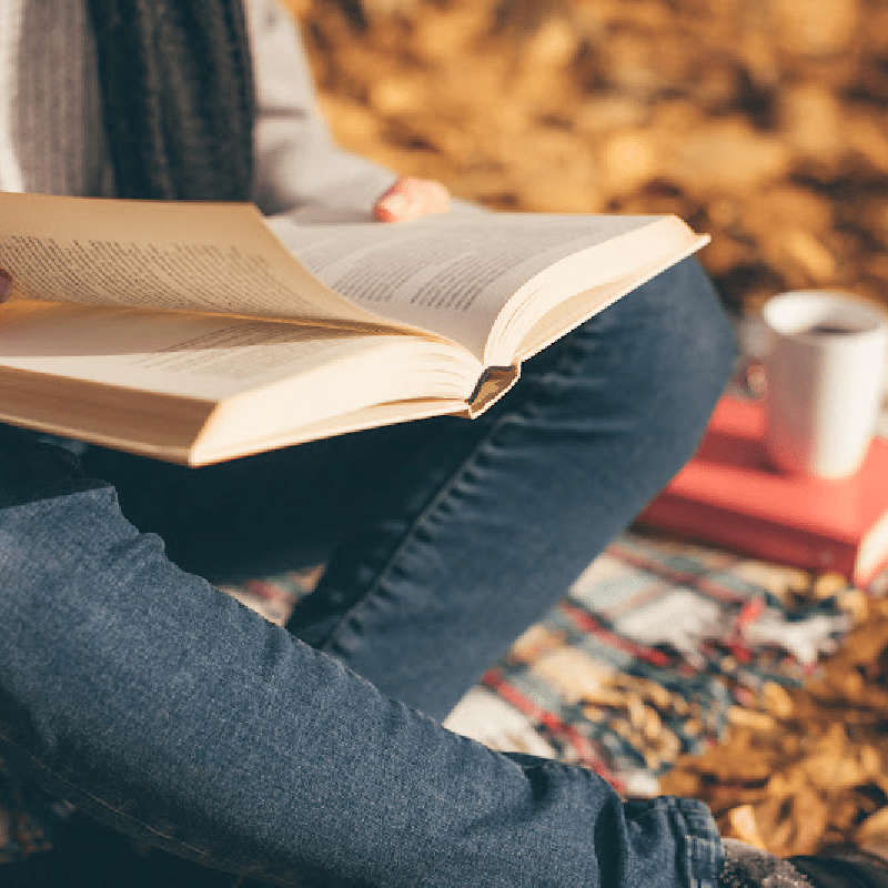 Reading outside in the fall with cup of coffee