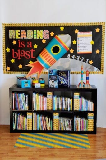 """Black classroom bookshelf with """"reading is a blast"""" space wall display"""