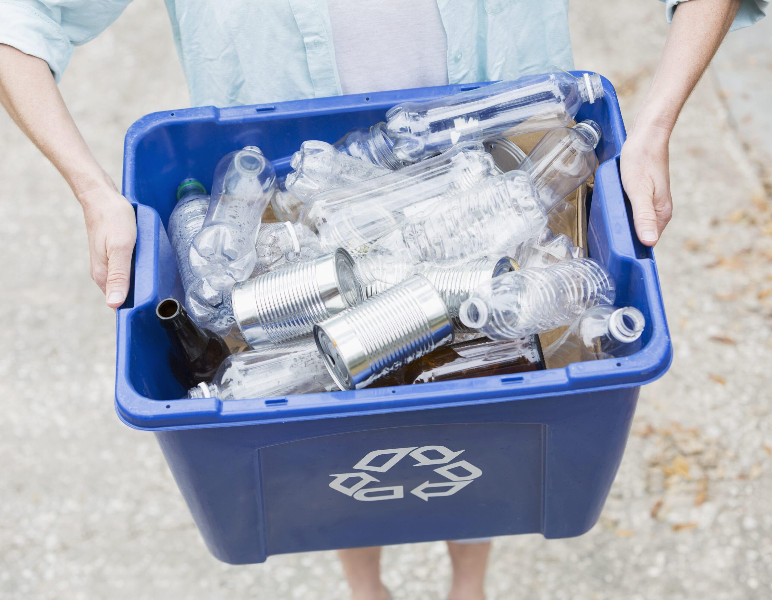 Woman carrying recycle bin