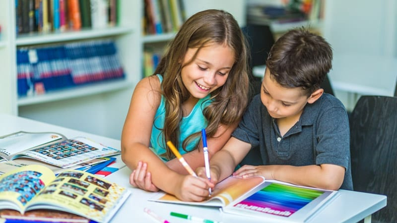 two children creating a yearbook with markers
