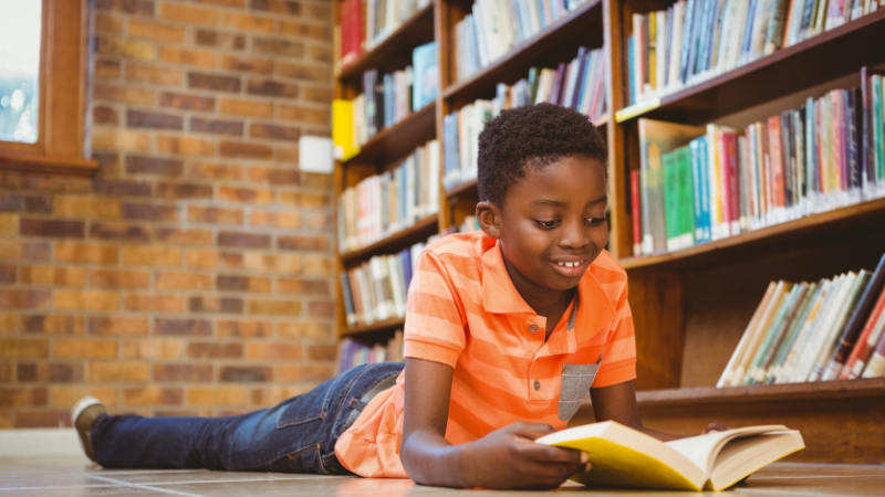 African American boy laying on ground in library reading a book - popular kids books