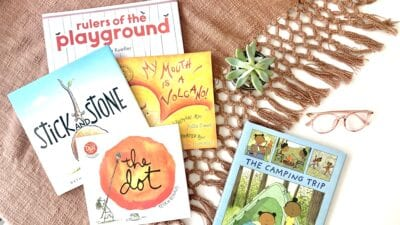 Five social emotional books laid out on a mauve blanket with reading glasses and a succulent.