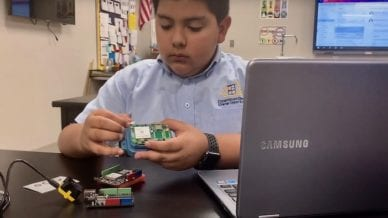 A boy putting together a circuit device