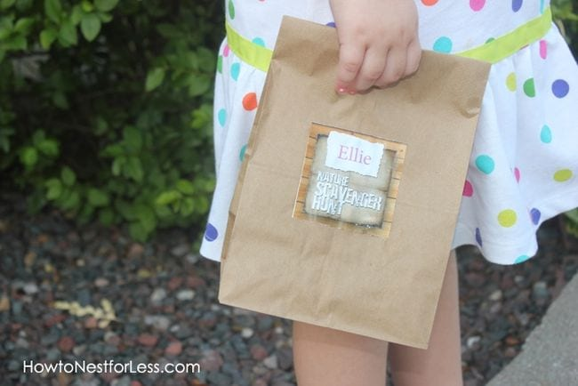"Child holding a paper bag labeled ""Ellie: Nature Scavenger Hunt"""