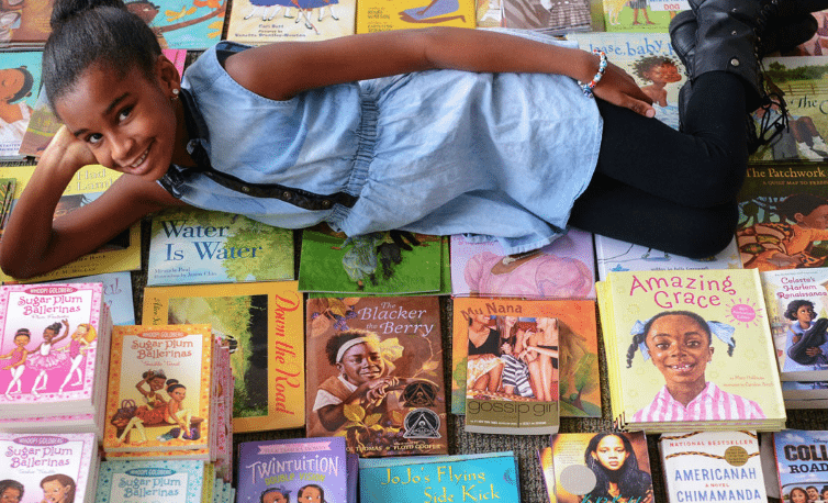 Marley Dias lying atop books with Black female characters