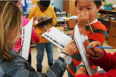 Students holding clipboards and look at the time on each other's paper watches (Telling Time)