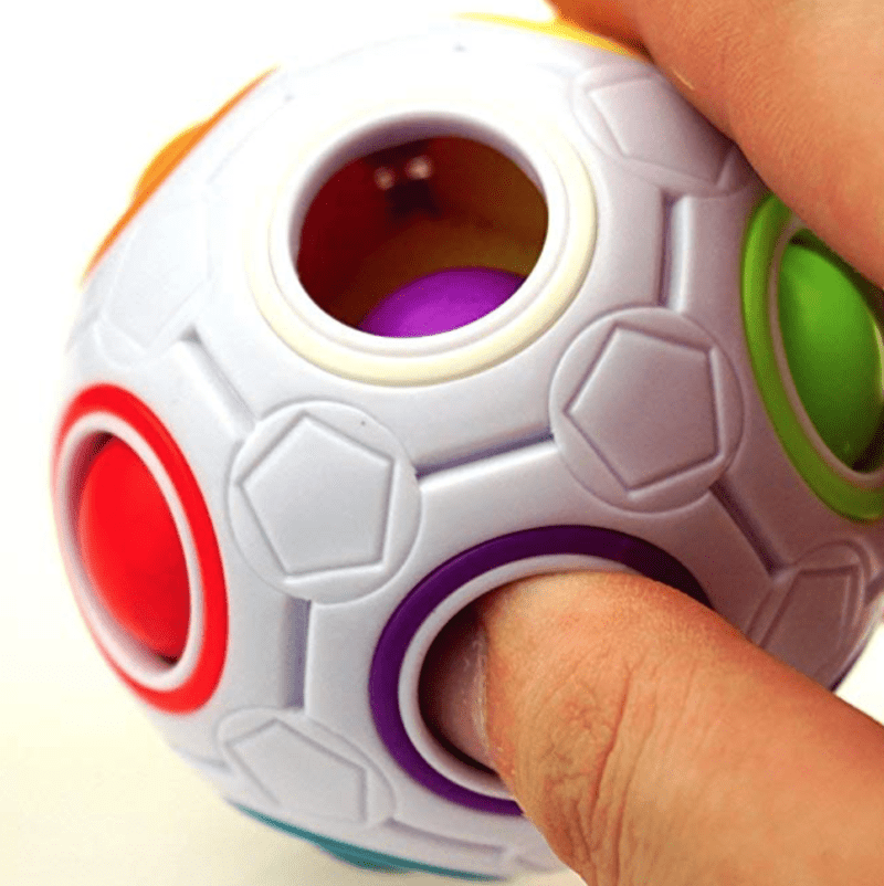 Student playing with a white plastic ball with holes filled with smaller colorful rubber balls