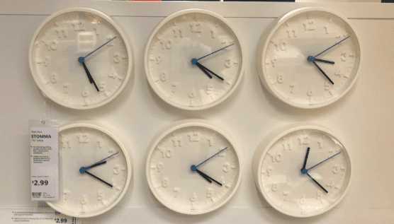 6 white plastic clocks displayed on a white wall