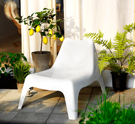 White plastic low chair next to plants
