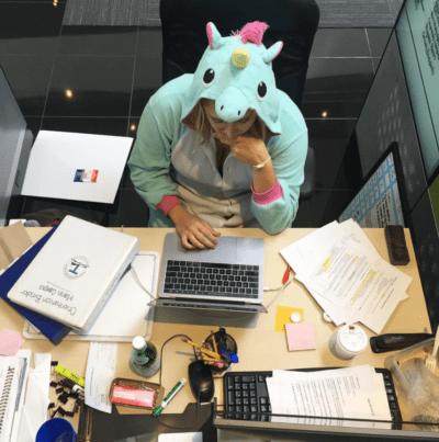 Educator in unicorn onesie working hard at her desk.