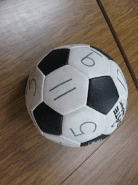 Soccer ball with multiplication problems written in white squares