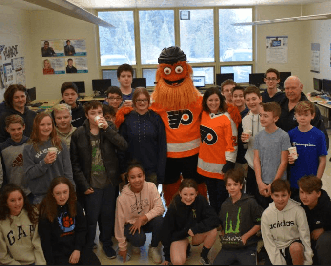 Group of school children gathered around Philadelphia Flyers mascot Gritty