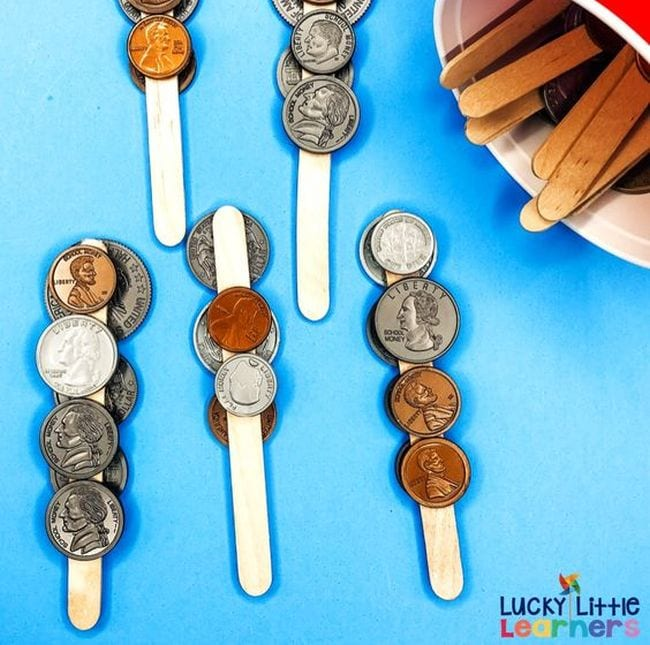 Wood craft sticks with plastic coins glued to them