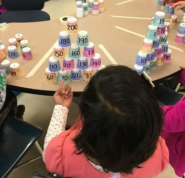 Second grade math students stacking paper cups labeled with numbers into pyramids
