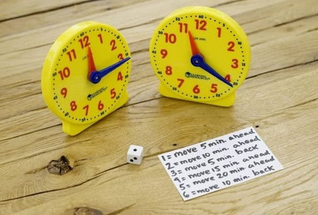 Two plastic toy clocks with a die and card with instructions for playing the game