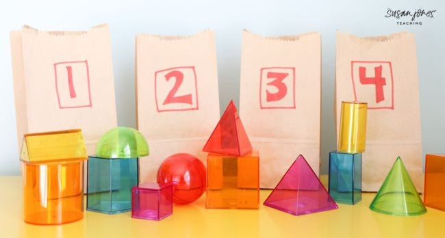 Colorful transparent 3-D shape blocks in front of paper bags numbered one through four (Second Grade Math Games)