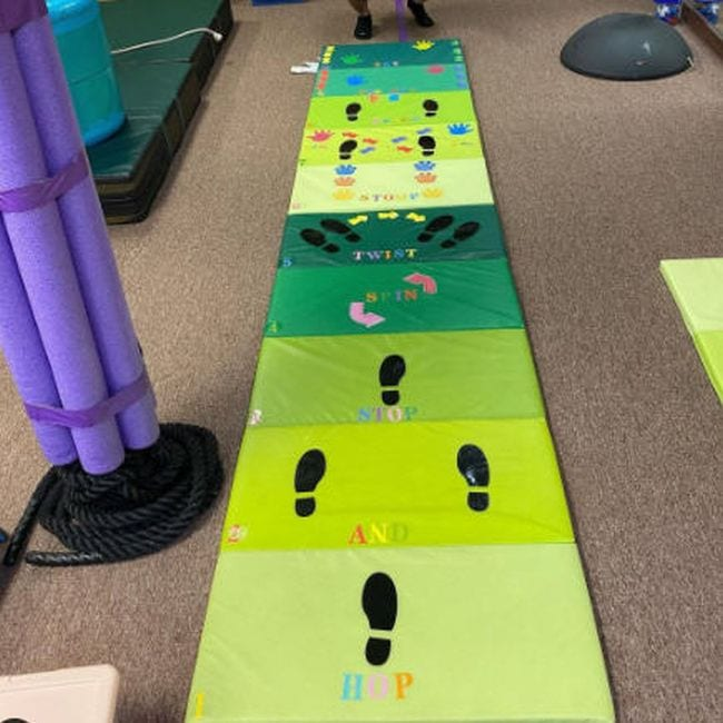 Foldable gym mat in shades of green marked with footprints and handprints