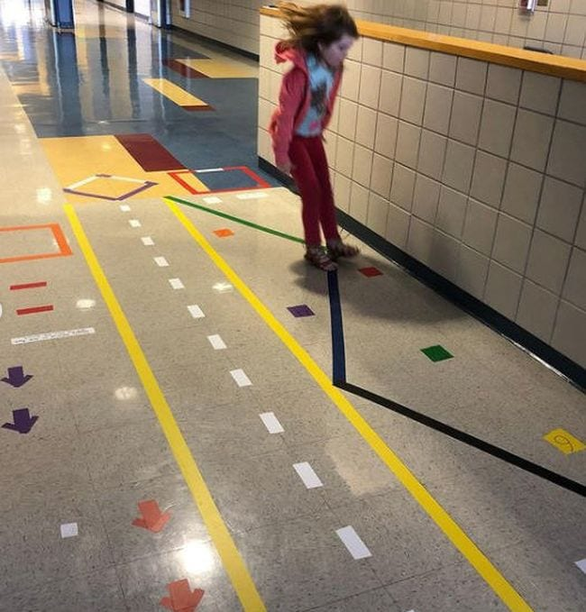 Tape lines on hallway floor marking running lanes, balance lines, and jumping spots