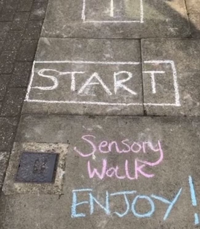 Sidewalk decorated with a sensory walk showing block saying start