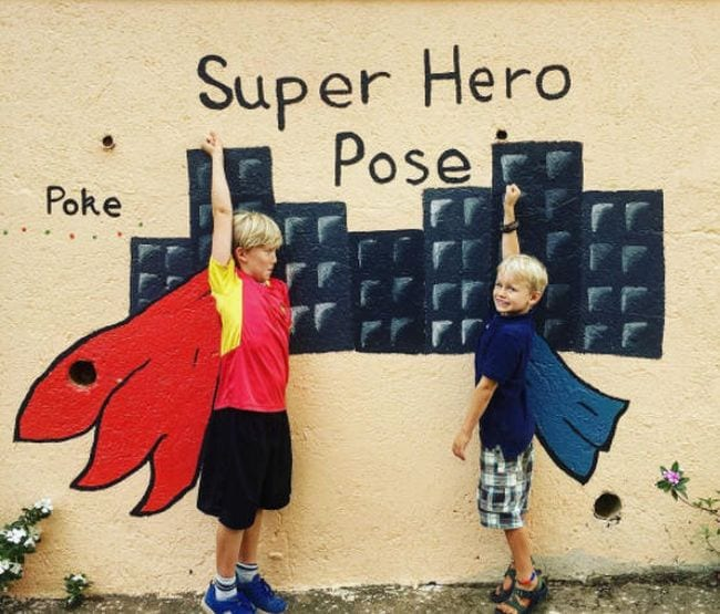 Two kids posing in front of capes and a cityscape painted on a wall
